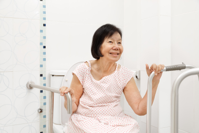 elder woman holding on handrail in toilet at home