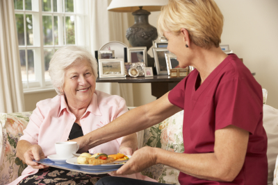 caregiver preparing meal for elder woman