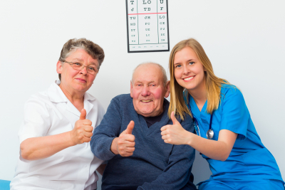caregiver and elderly couple showing their thumbs up